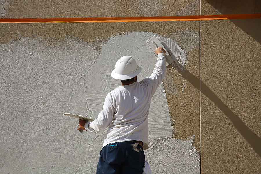 worker putting stucco cement on wall