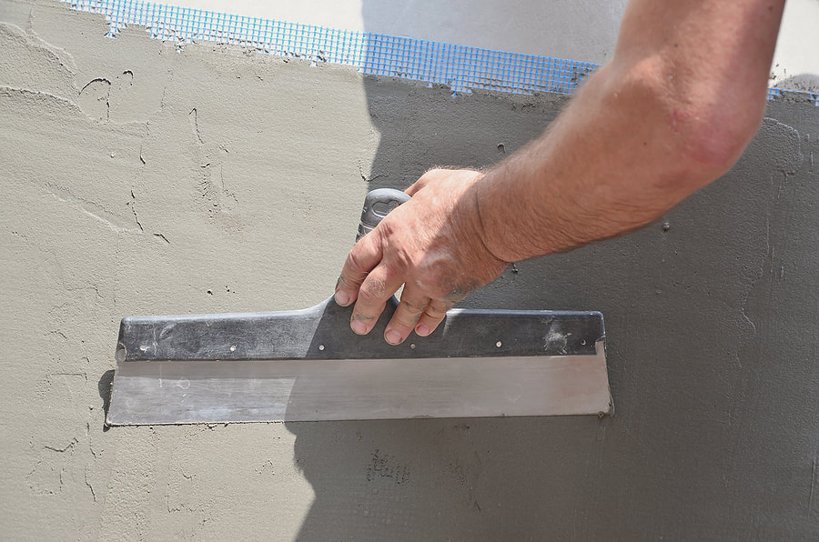 worker finishing the stucco cement on wall