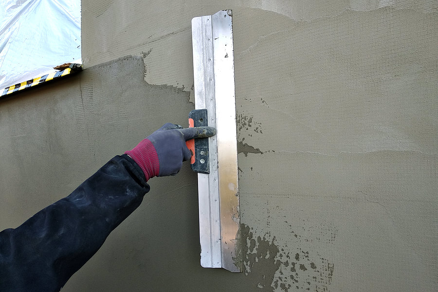 worker installing stucco cement on wall