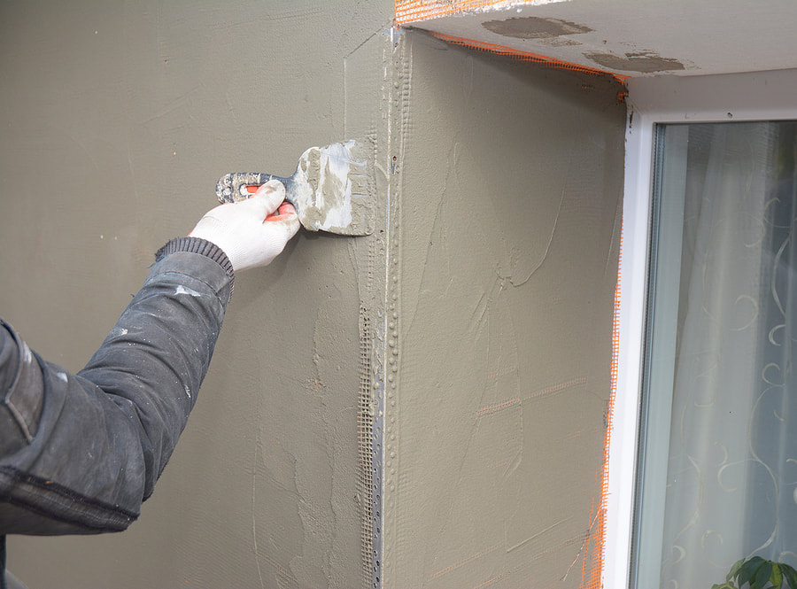 worker putting stucco cement on wall edge